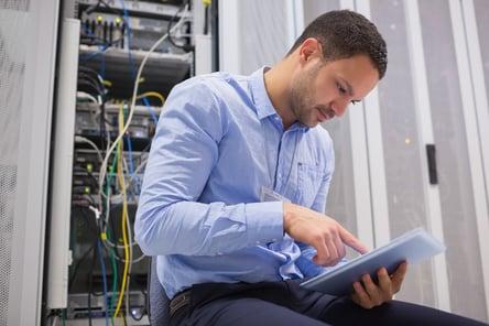 Man using tablet pc beside servers in data center