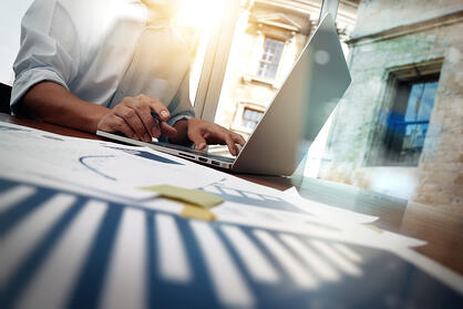 business documents on office table with smart phone and digital tablet and graph financial diagram and man working in the background-1